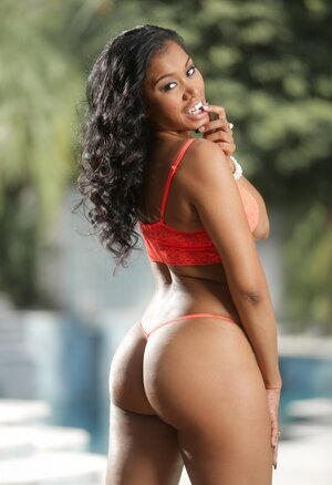 Curly-haired Ebony female provocatively shows assets outdoors under sun