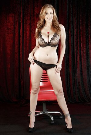 Female sits on a red stool and takes clothes off element by element leaving high heels on