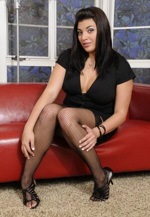 Breasty Latina in fishnet stockings has fun with huge dildos on red couch