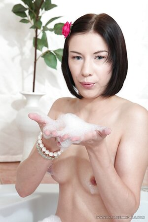 Russian girl with Asian roots Kira Doll poses nicely in the foamy bathtub