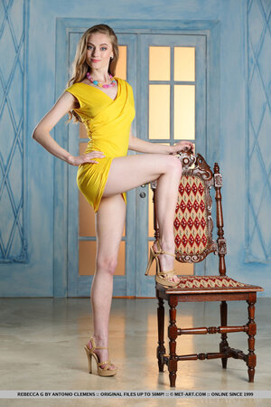 Young model removes tight yellow dress and matching-color panties on the chair