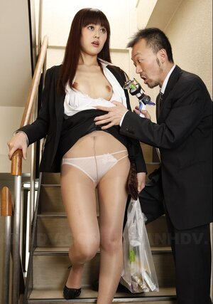 Dude in a suit takes off Asian's nylons on the stairs and aims strange toy at it
