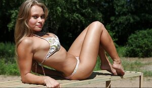 Fascinating young-looking female with pretty titties lies on an outdoor bench sunbathing