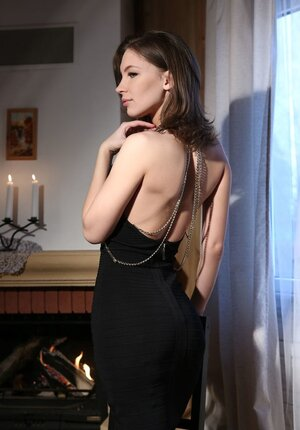 Cuddly lecher in a slinky black dress exposes trimmed snatch on a chair